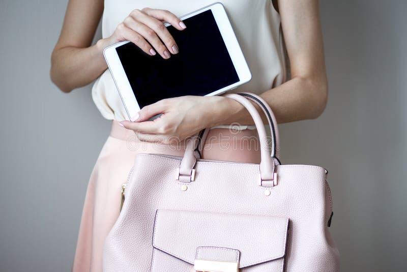 Tableta electrónica de Digitaces en las manos del ` un s de la mujer Bolso rosa claro de cuero, estilo elegante del verano fotos de archivo