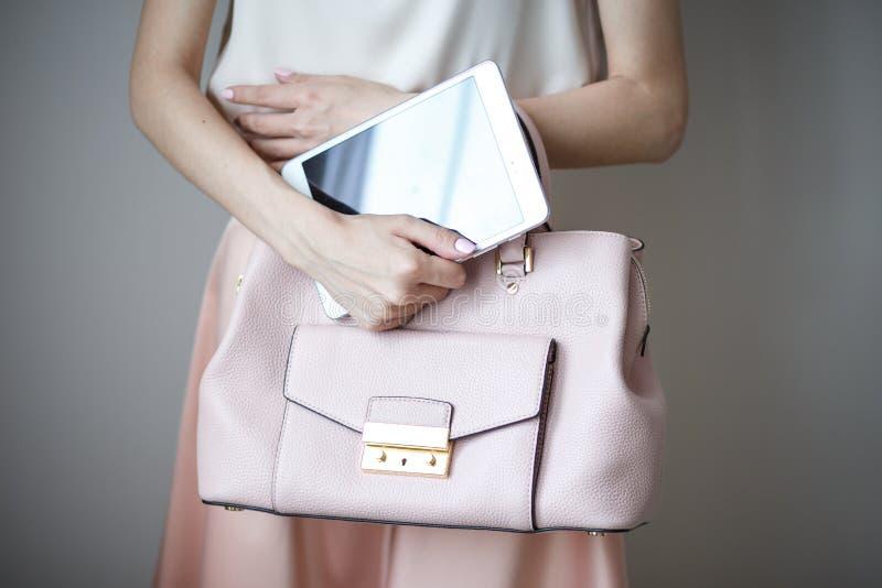 Tableta electrónica de Digitaces en las manos del ` un s de la mujer Bolso rosa claro de cuero, estilo elegante del verano fotografía de archivo