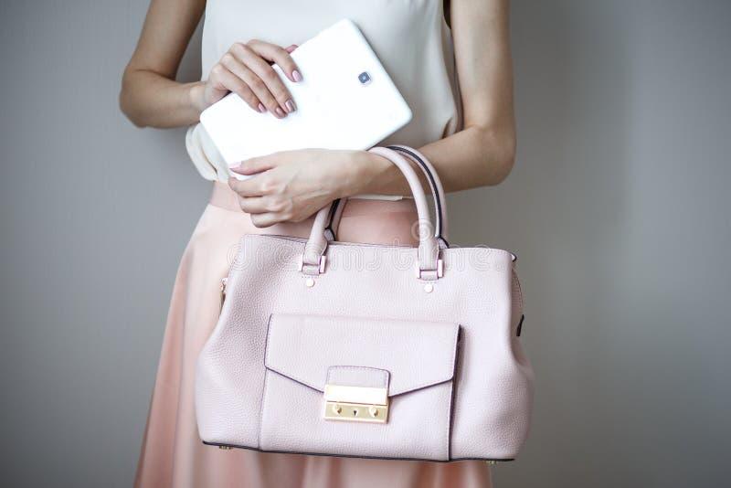 Tableta electrónica de Digitaces en las manos del ` un s de la mujer Bolso rosa claro de cuero, estilo elegante del verano imagen de archivo