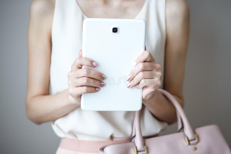 Tableta electrónica de Digitaces en las manos del ` un s de la mujer Bolso rosa claro de cuero, estilo elegante del verano imagenes de archivo