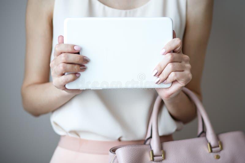 Tableta electrónica de Digitaces en las manos del ` un s de la mujer Bolso rosa claro de cuero, estilo elegante del verano fotos de archivo libres de regalías