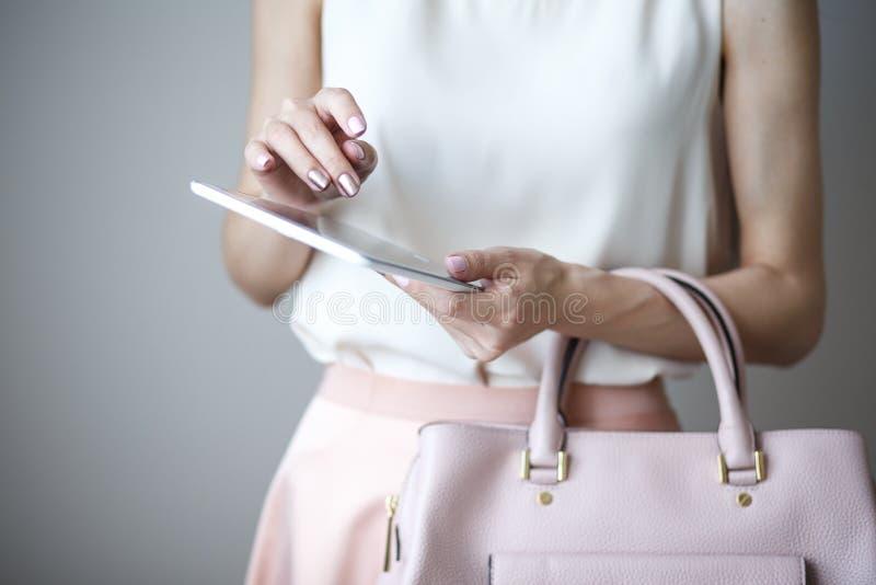 Tableta electrónica de Digitaces en las manos del ` un s de la mujer Bolso rosa claro de cuero, estilo elegante del verano foto de archivo