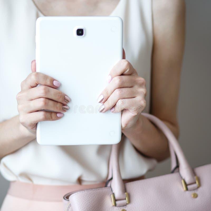 Tableta electrónica de Digitaces en las manos del ` un s de la mujer Bolso rosa claro de cuero, estilo elegante del verano imágenes de archivo libres de regalías