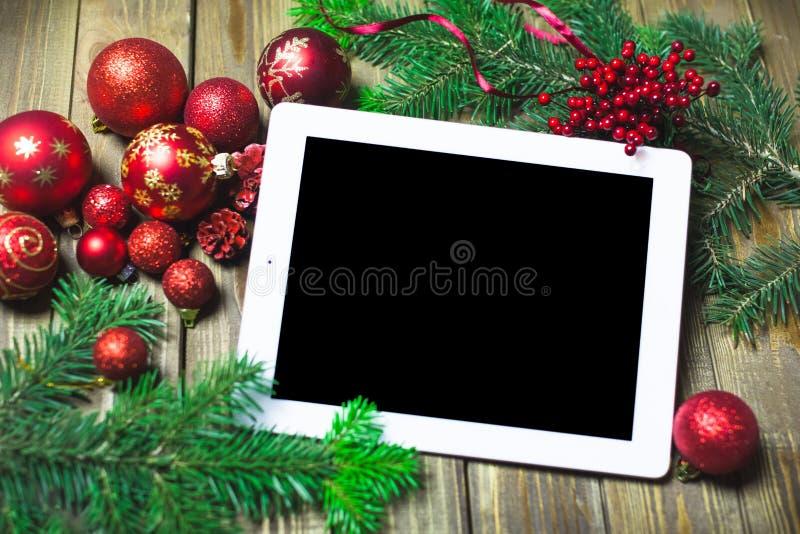 Tableta en blanco rodeada por la Navidad foto de archivo libre de regalías