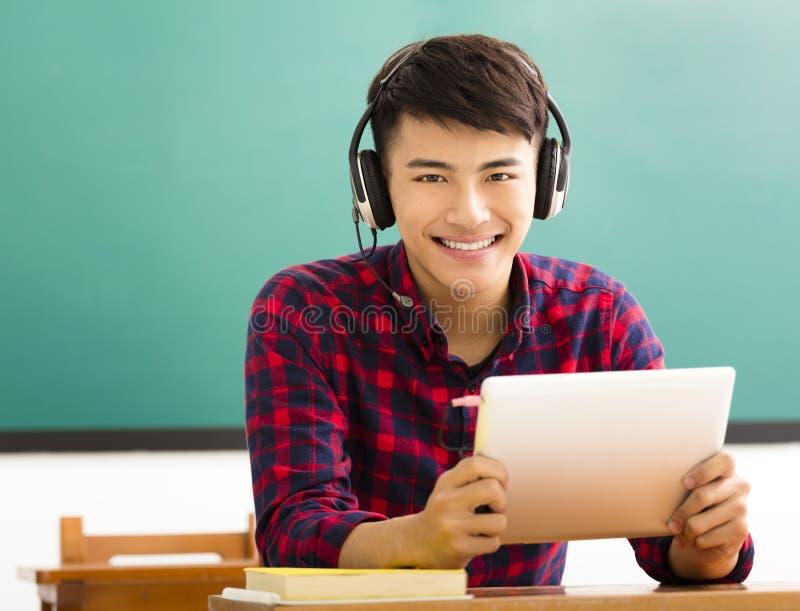 Tableta feliz de la lectura del estudiante en sala de clase imagenes de archivo
