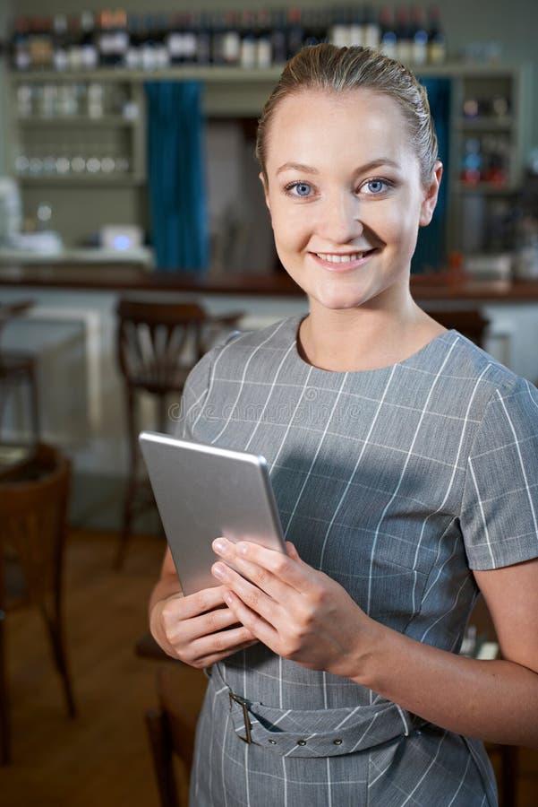 Tableta femenina de In Restaurant With Digital del encargado foto de archivo