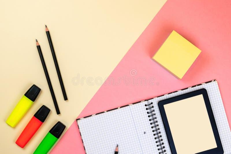 Tableta, fuentes de escuela, cuaderno y marcadores coloreados en fondo rosado y beige en colores pastel foto de archivo
