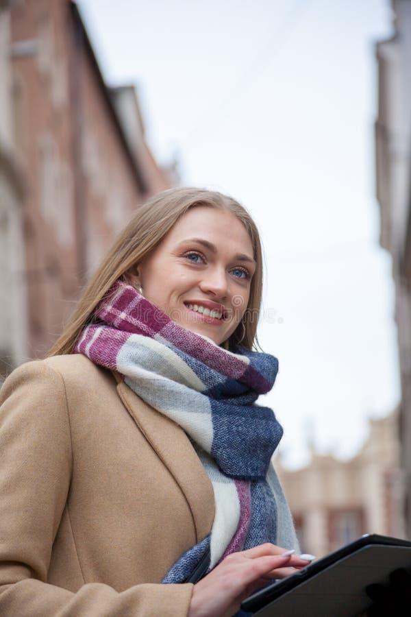 Tableta hermosa rubia sonriente de la tenencia de la mujer en la calle de la ciudad fotografía de archivo libre de regalías