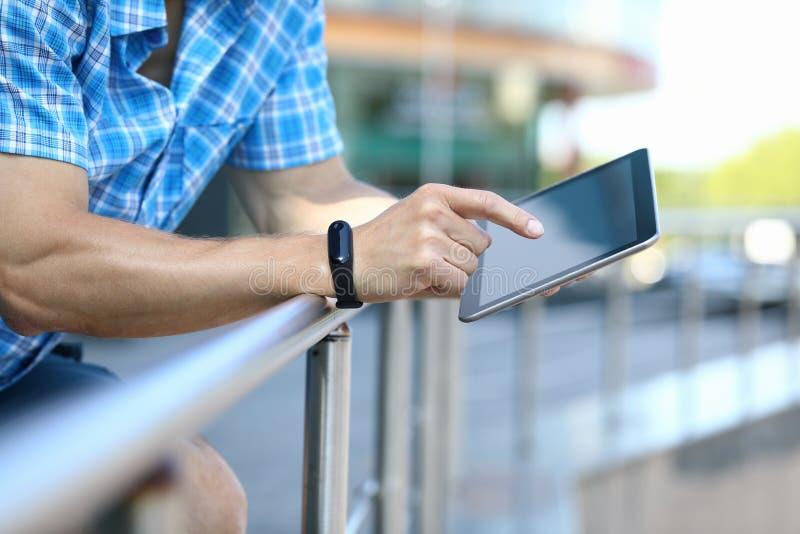 Tableta masculina del control del hombre de negocios a disposición contra foto de archivo