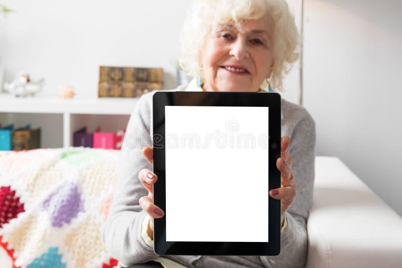 Tableta mayor de la demostración de la mujer fotografía de archivo libre de regalías
