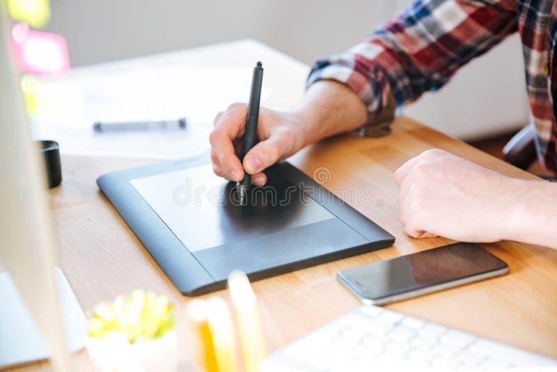 Tableta negra de la pluma con la aguja usada por la mano masculina del diseñador imagen de archivo libre de regalías