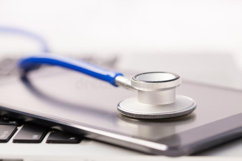 Tableta/Phablet que es diagnosticado por el estetoscopio - llame por teléfono a la reparación a imagenes de archivo