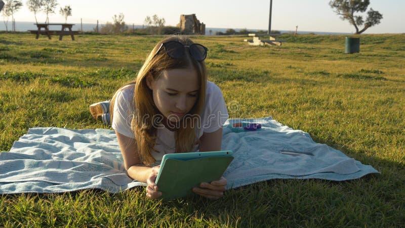 Tableta que usa femenina en el parque con el mar en el horizonte imagenes de archivo