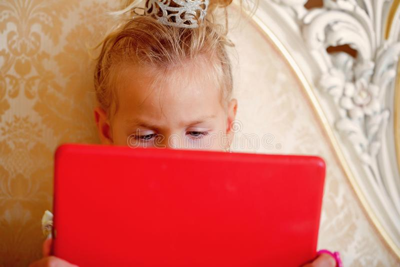 Tableta roja del uso del niño de la muchacha en el sofá foto de archivo libre de regalías