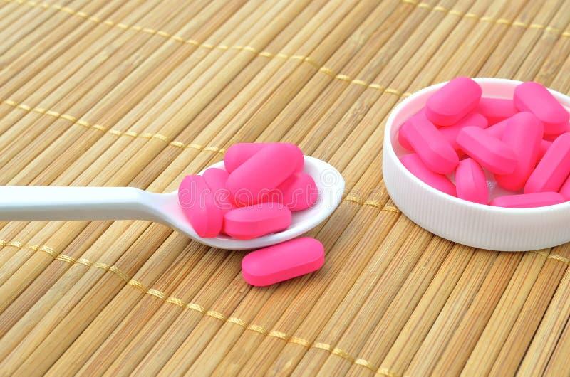 Tableta rosada de la medicina en la cuchara foto de archivo libre de regalías