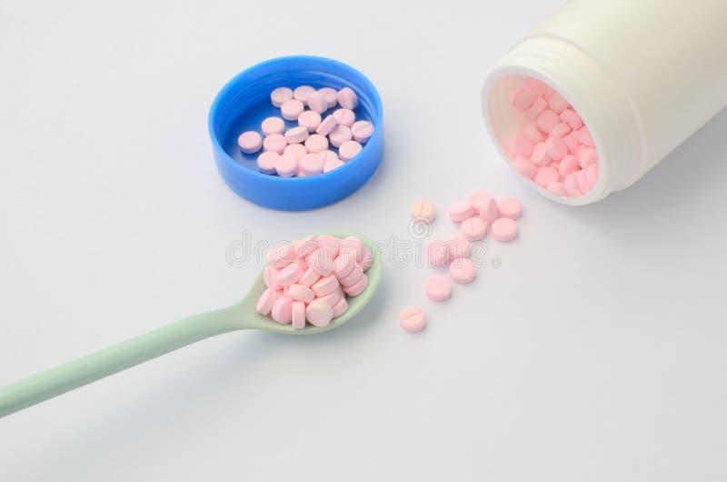 Tableta rosada de la medicina en la cuchara y la botella abierta de medicina fotografía de archivo