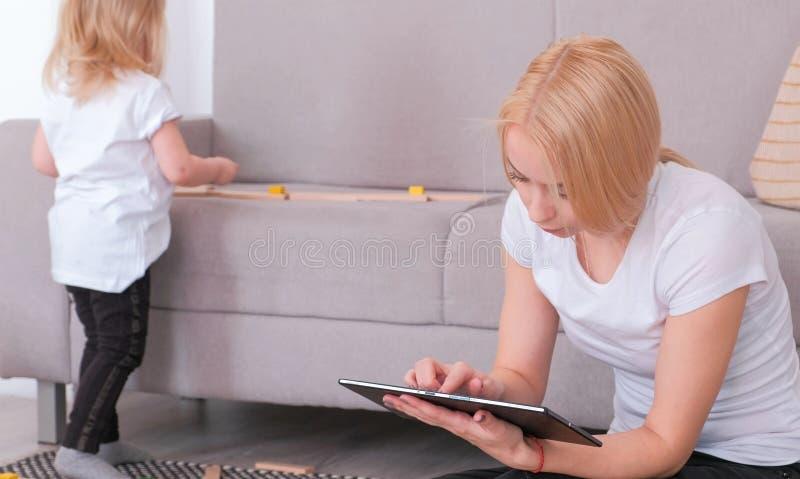 Tableta rubia atractiva joven de la ojeada de la mamá mientras que su hija encantadora que juega bloques de madera foto de archivo libre de regalías