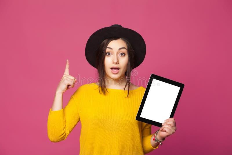 Tableta sonriente de la tenencia de la mujer que tiene nueva idea imagen de archivo