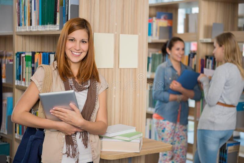 Tableta sonriente de la tenencia del estudiante universitario en biblioteca foto de archivo