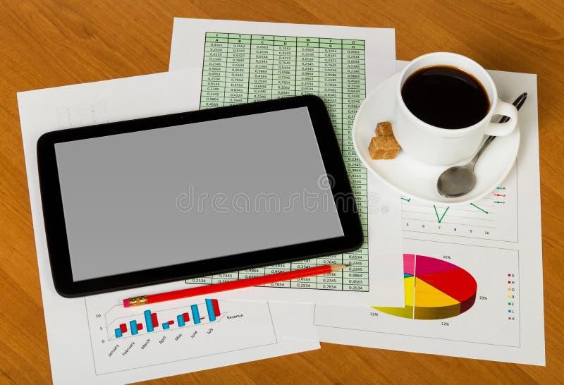 Tableta, taza de café y dulzor, cuchara, lápiz, hojas del PA fotografía de archivo