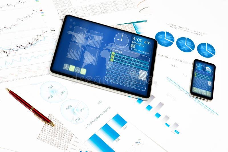 Tableta, teléfono celular y documentos financieros imágenes de archivo libres de regalías