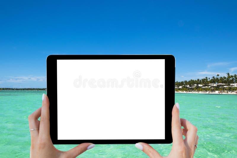 Tableta vacía en blanco en las manos de la muchacha en la playa tropical del océano de la turquesa Pantalla blanca aislada Espaci imagen de archivo