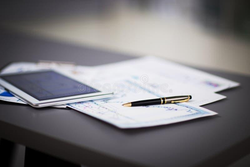 Tableta y diagramas financieros en el lugar de trabajo imagen de archivo