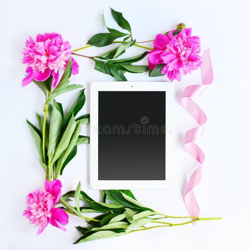 Tableta y flores rosadas fotografía de archivo libre de regalías