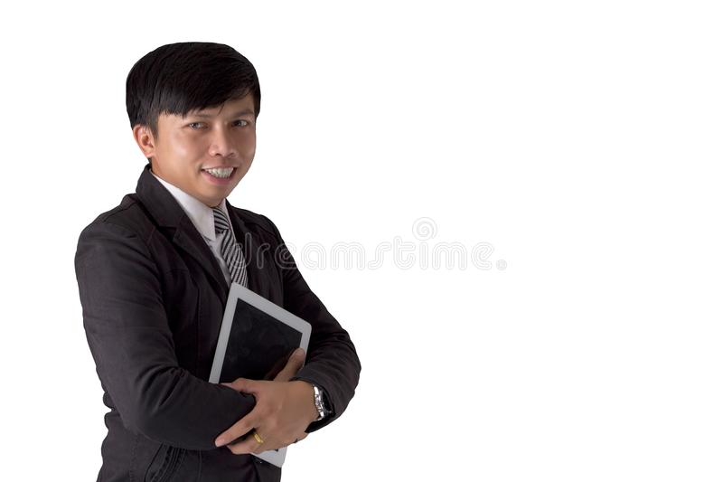 Tableta y sonrisa de la tenencia del traje del hombre joven de Asia del retrato que lleva foto de archivo libre de regalías