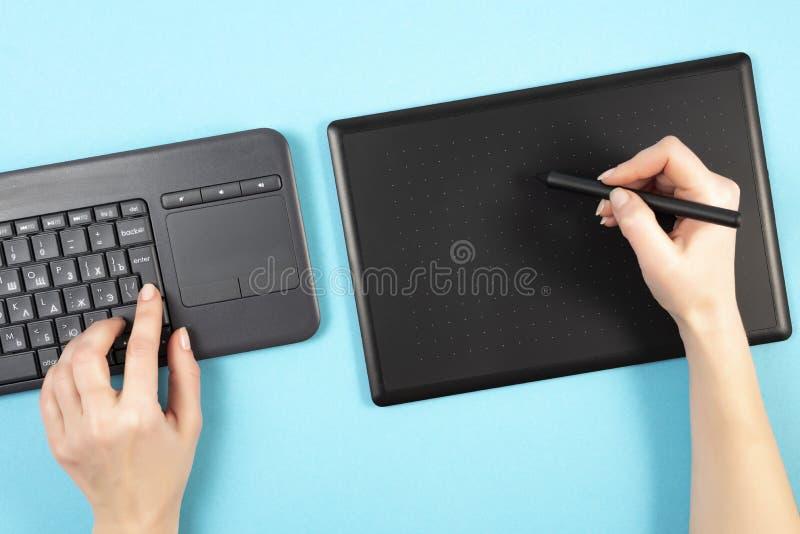 Tableta y teclado de gráficos en un fondo azul Espacio para el texto Teclado imagen de archivo