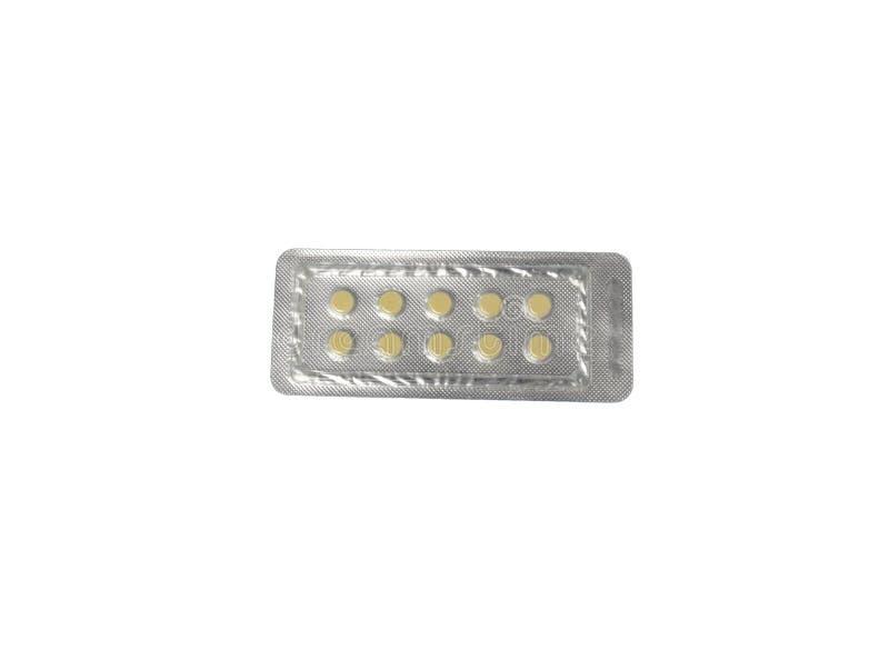 Tabletas amarillas en ampollas en un primer blanco del fondo imagen de archivo