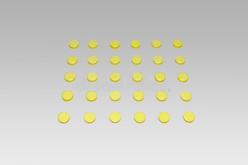 Tabletas, dispuestas en matriz cuadrada de la forma aseada Amarillo coloreado imagen de archivo