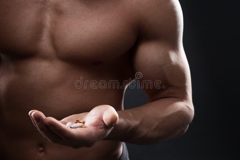 Tabletas en la mano de un atleta foto de archivo