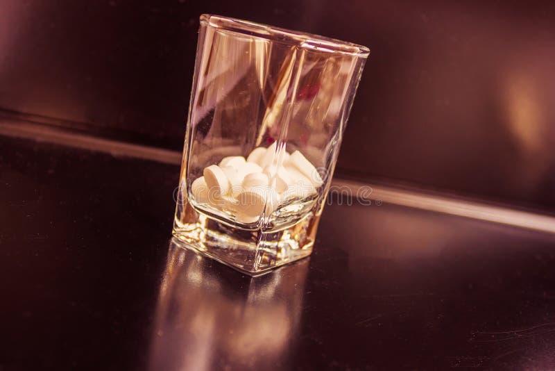 Tabletas en un vidrio de la vodka fotografía de archivo libre de regalías
