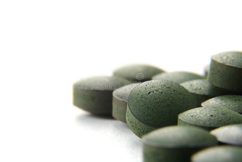 Tabletas orgánicas puras de Spirulina sobre el fondo blanco, Su dietético fotos de archivo