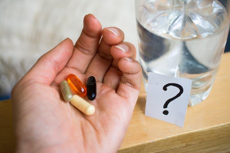 Tabletas, píldoras a disposición cerca de un vidrio de agua y signo de interrogación foto de archivo