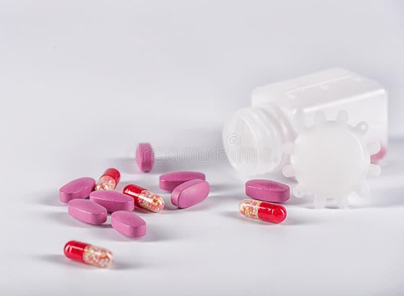 Tabletas rosadas y píldoras rojas cerca de la botella plástica de mentira imagenes de archivo