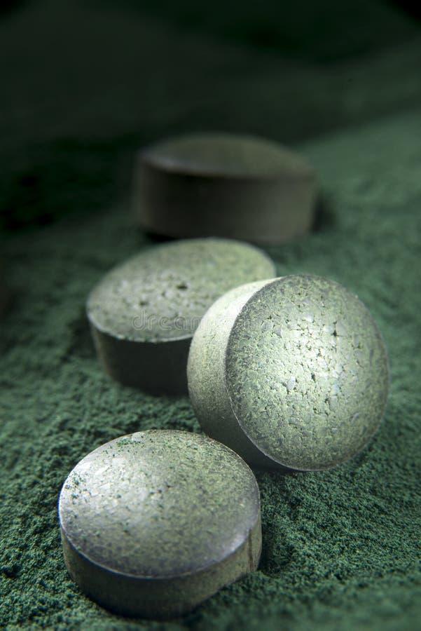 Tabletas y polvo, suplemento dietético de Spirulina imagenes de archivo