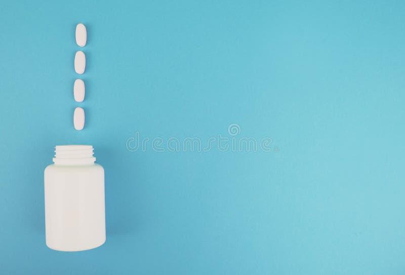Tabletas y una botella para las medicinas en un fondo azul Lugar para la firma El concepto de tratar enfermedad cardíaca imagen de archivo
