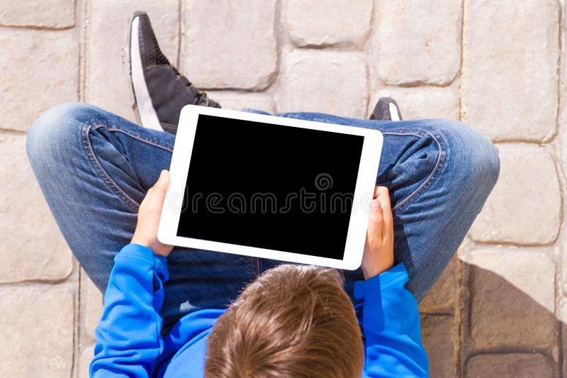 Tabletcomputer in de handen van een kind dat zitting ter plaatse stock foto's