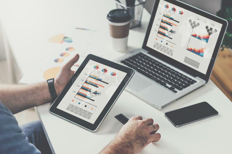 Tabletcomputer met grafieken, diagrammen en grafieken op het scherm in handen van jonge gebaarde zakenmanzitting bij lijst stock afbeeldingen