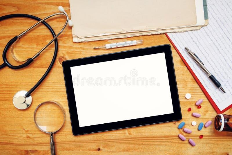 Tabletcomputer met het lege scherm op doctor& x27; s bureau stock foto