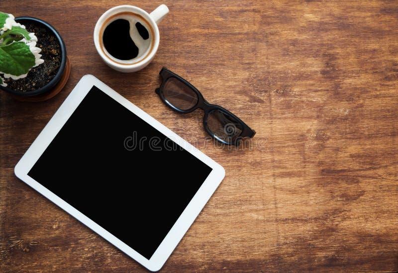 Tabletleerer bildschirm, schwarzer Glastasse kaffee und grüne Blume auf hölzernem Schreibtisch Kopieren Sie Platz Flache Lage lizenzfreie stockbilder