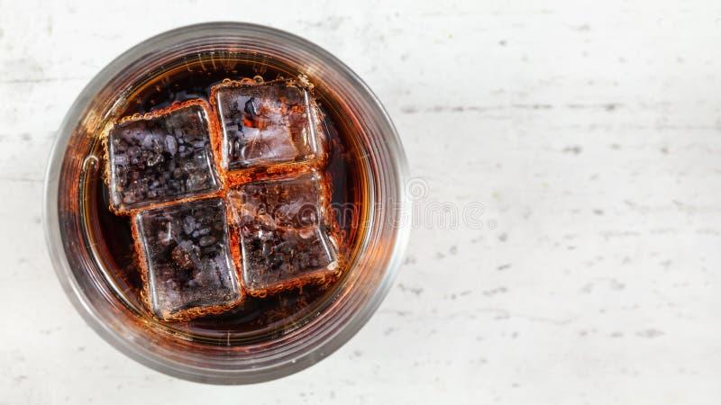 Tabletop foto, exponeringsglas med cola och fyra iskuber p? det vita br?det, utrymme f?r textr?tt arkivbilder