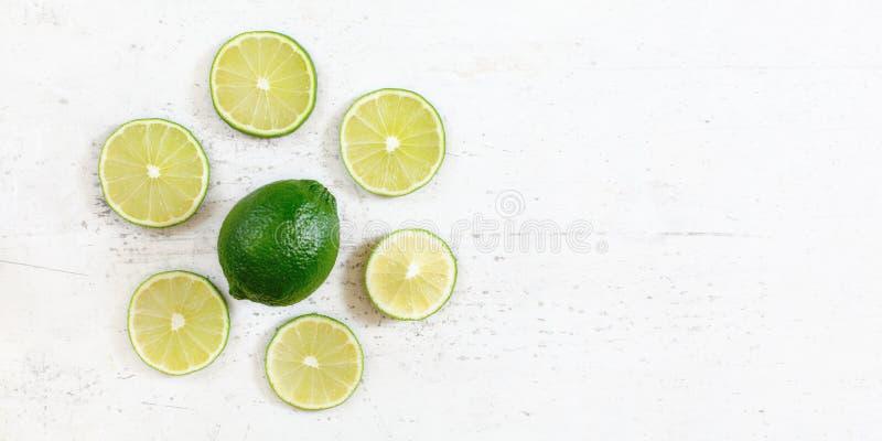 Tabletop foto, hel gr?n limefrukt med skivad frukt omkring, p? det vita funktionsdugliga br?det, utrymme f?r textr?tt arkivfoton