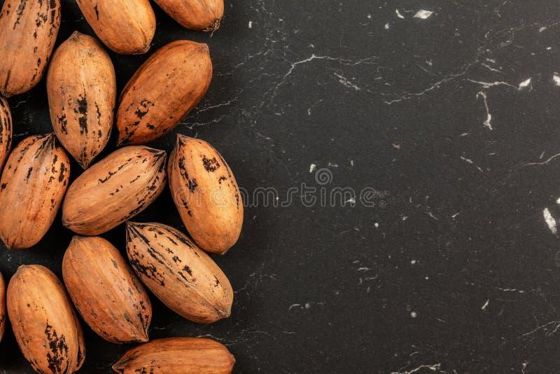 Tabletop foto - hela pecannötmuttrar på svart marmor som brädet, utrymme för texträtsida royaltyfri foto