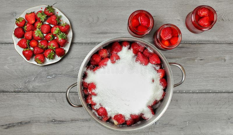 Tabletop photo - large steel pot of strawberries covered with crystal sugar, plate and glass bottles with more fruits around on royalty free stock image