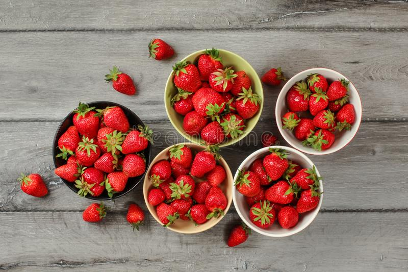 Tabletop sikt - fem lilla bunkar med jordgubbar, några av dem spillde på det gråa träskrivbordet arkivfoton