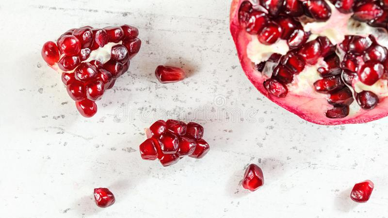 Tabletop sikt, granatäpple, ädelsten som frukter spridda på det vita konkreta brädet fotografering för bildbyråer