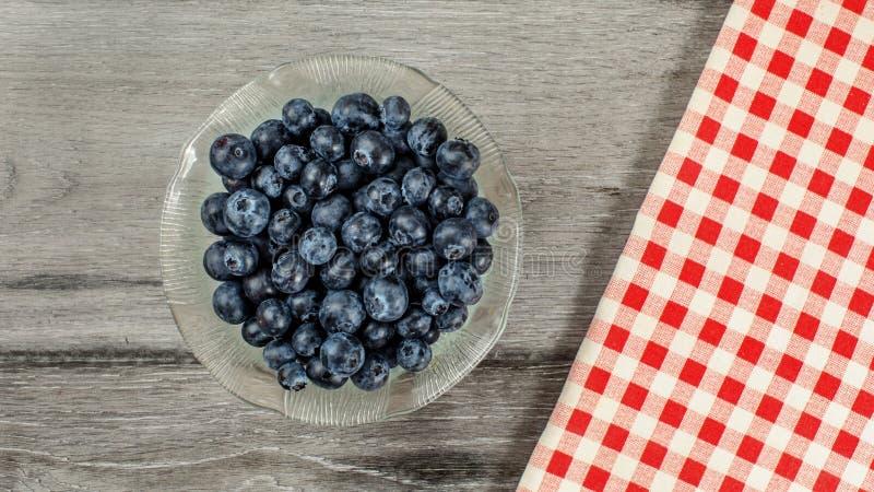 Tabletop sikt, liten exponeringsglasbunke av blåbär, röd rutig ginghambordduk bredvid den på det gråa träskrivbordet royaltyfria bilder